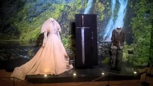 Robe de Sansa Stark à gauche, habits d'Arya Stark sur la droite, au milieu Glace, l'épée d'Eddard Stark, et Aiguille, l'épée d'Arya - Expo GoT